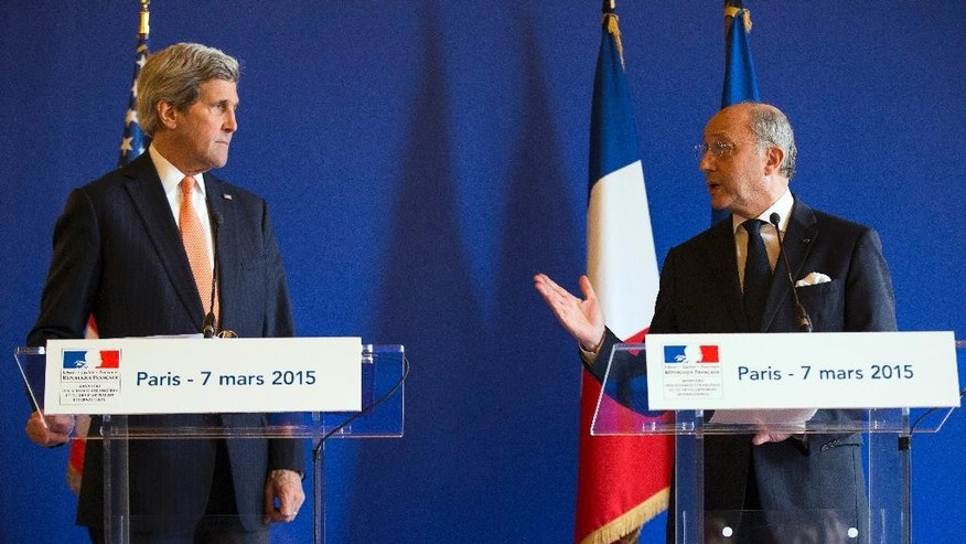 Secretary of State John Kerry, left, listens to French Foreign Minister Laurent Fabius during a news conference, on Saturday, March 7, 2015, in Paris. Kerry is meeting with the foreign ministers of France, Germany, and Britain to brief them on the status of nuclear negotiations with Iran. (AP Photo/Evan Vucci)