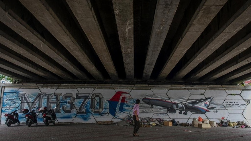 An unidentified man walks past MH370 related street art under a flyover in Kuala Lumpur, Malaysia on Friday, March 6, 2015. (AP Photo/Joshua Paul)