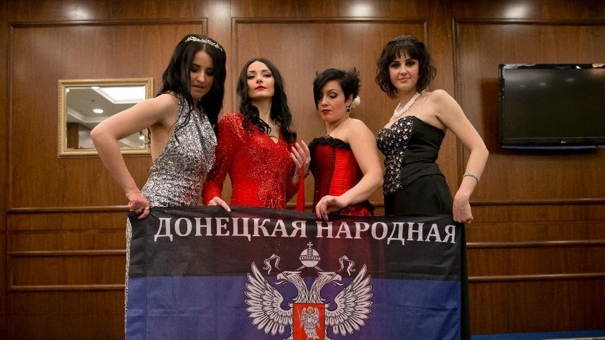 Russia-backed female rebel fighters pose with the flag of the Donetsk People's Republic during a beauty contest involving women from the main separatist battalions in Donetsk, Ukraine, Saturday, March 7, 2015. Self-proclaimed authorities in the rebel-held Donetsk held a beauty pageant for female rebel fighters on the eve of March 8, a women's day widely celebrated throughout the former Soviet Union.(AP Photo/Vadim Ghirda)