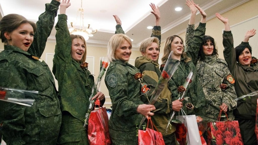 Russia-backed female rebel fighters wave while posing for media after a beauty contest involving women from the main separatist battalions in Donetsk, Ukraine, Saturday, March 7, 2015. Self-proclaimed authorities in the rebel-held Donetsk held a beauty pageant for female rebel fighters on the eve of March 8, a women's day widely celebrated throughout the former Soviet Union.(AP Photo/Vadim Ghirda)