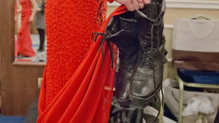 A Russia-backed female rebel fighter holds military boots as she prepares to go on stage during a beauty contest involving women from the main separatist battalions in Donetsk, Ukraine, Saturday, March 7, 2015. Self-proclaimed authorities in the rebel-held Donetsk held a beauty pageant for female rebel fighters on the eve of March 8, a women's day widely celebrated throughout the former Soviet Union.(AP Photo/Vadim Ghirda)