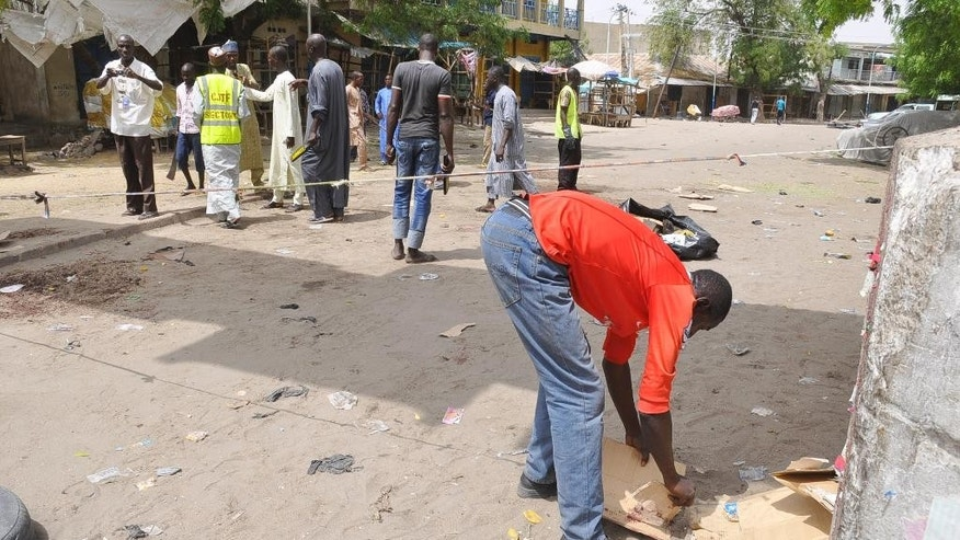 People gather at the site of a bomb explosion at a market in Maiduguri, Nigeria, Saturday, March 7, 2015 .Two blasts killed more than 10 people on Saturday in a busy marketplace in Maiduguri, the biggest city in northeastern Nigeria, say witnesses. (AP Photo/Jossy Ola)