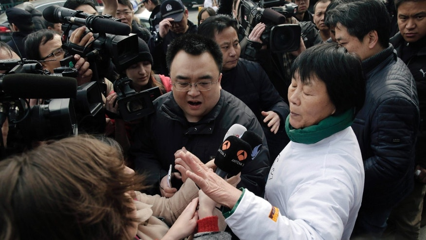 March 8, 2015: Dai Shuqin, front right, and Jiang Hui, rear right, relatives of passengers on board the Malaysia Airlines Flight 370 that went missing on March 8, 2014, is intervened by policemen as they try to speak to journalists near Yonghegong Lama Temple during a gathering of family members of the missing passengers.