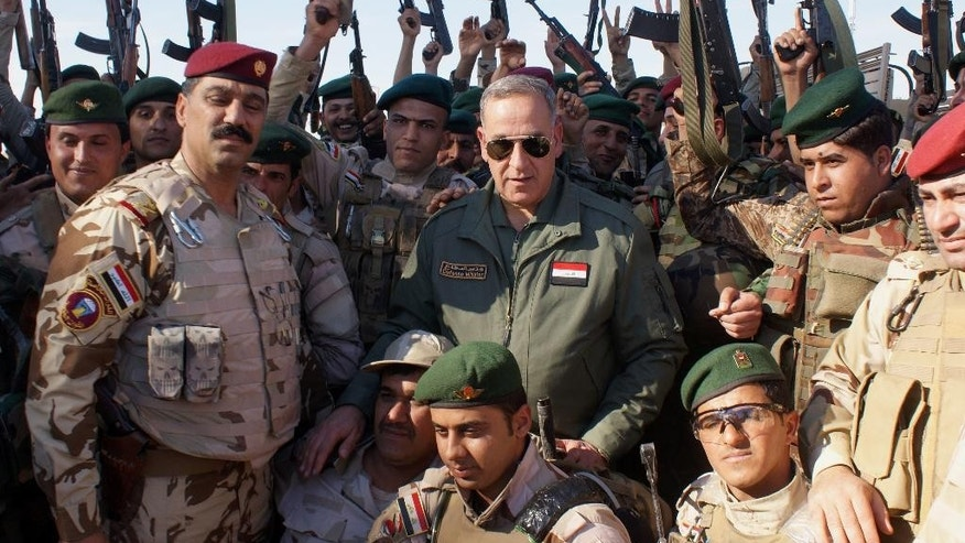 March 7, 2015: Iraqi Defense Minister Khalid al-Obeidi, center, surrounded by soldiers, as they pose for a group photograph at the Iraqi Army headquarters in Samarra, 60 miles north of Baghdad, Iraq. (AP)