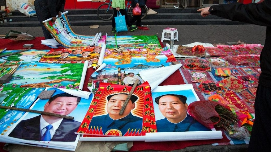In this photo taken Feb. 5, 2015, vendors sell posters of Chinese President Xi Jinping and late leader Mao Zedong on a street of Gujiao in northern China's Shanxi province. Barely two years into office, Xi has attracted an extraordinary degree of attention to his public persona that veers perilously close to a full-blown personality cult. Such a phenomenon has not seen since the days of Mao Zedong, with successors wary of the turmoil his leadership unleashed and generally favoring a dry, rule-by-consensus approach. (AP Photo/Ng Han Guan)