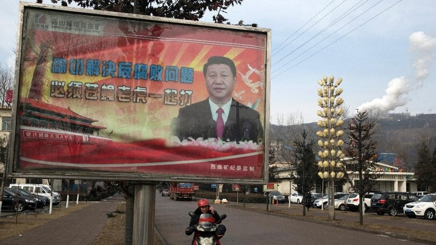 "In this photo taken Feb. 6, 2015, a motorcyclist speaks on his phone near a billboard showing Chinese President Xi Jinping with the slogan ""To exactly solve the problem of corruption, we must hit both flies and tigers"" in Gujiao in northern China's Shanxi province.  Barely two years into office, Xi has attracted an extraordinary degree of attention to his public persona that veers perilously close to a full-blown personality cult. Such a phenomenon has not seen since the days of Mao Zedong, with successors wary of the turmoil his leadership unleashed and generally favoring a dry, rule-by-consensus approach. (AP Photo/Ng Han Guan)"