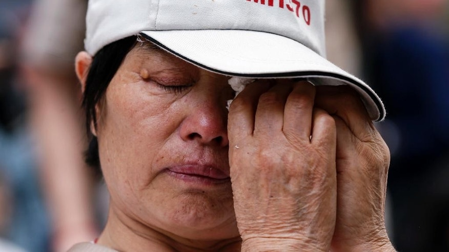 March 8, 2015: China's Wang Run Xiang, 58, whose son was one of the passengers on board Malaysia Airlines Flight 370, wipes her tears during a remembrance event in a mall outside Kuala Lumpur, Malaysia.