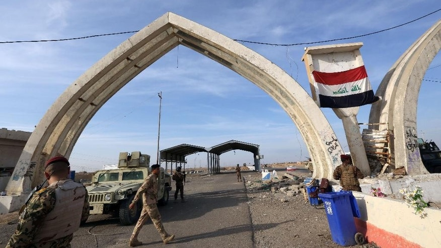 "FILE - In this file photo taken Monday, Dec. 8, 2014, Iraqi security forces and Shiite fighters are deployed during a military operation to regain control of the university of Tikrit, 80 miles (130 kilometers) north of Baghdad, Iraq. On Wednesday, March 4, 2015, New York-based Human Rights Watch called on the Iraqi government to protect civilians in Tikrit and allow them to flee combat zones. Its statement noted ""numerous atrocities"" against Sunni civilians by pro-government militias and security forces, ranging from ""summary executions, revenge killings, or other abuses."" (AP Photo/Hadi Mizban, File)"