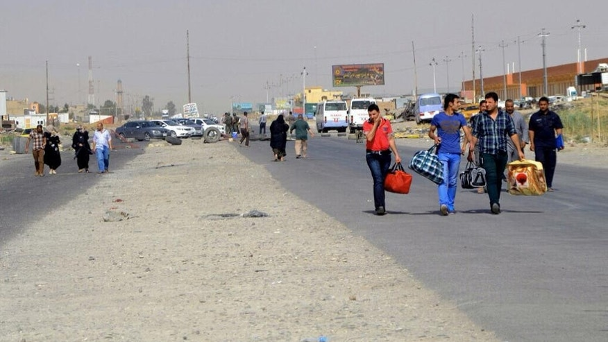FILE - In this file photo taken Sunday, June 29, 2014, Iraqis leave their hometown Mosul, walking towards Irbil, on the outskirts of the northern city of Mosul, Iraq. Sunni civilians still living under the Islamic State rule in northern Iraq fear that their eventual liberation could bring a new round of violence in the form of reprisal attacks. (AP Photo, File)