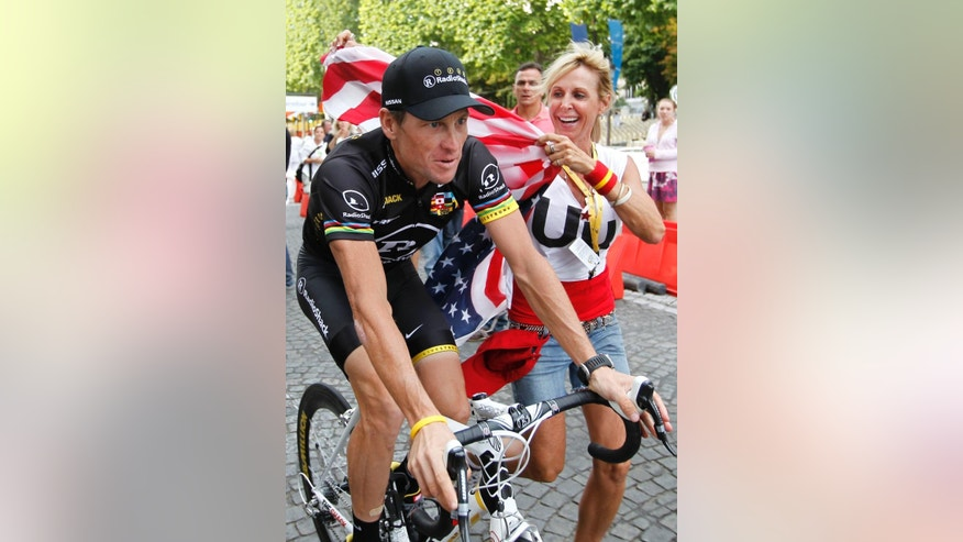FILE - A Sunday, July 25, 2010 photo from files showing a fan with an American flag running alongside Lance Armstrong of the US during the parade after the 20th and last stage of the Tour de France cycling race in Paris, France. Cycling leaders let doping flourish and broke their own rules so Lance Armstrong could cheat his way to become a superstar the sport badly needed, according to a scathing report into its drug culture published Monday, March 9, 2015. The International Cycling Union was severely criticized for failing to act during the doping era dominated by Armstrong, but the 227-page report found no evidence that he paid to cover up alleged positive tests. (AP Photo/Eric Gaillard, File Pool)