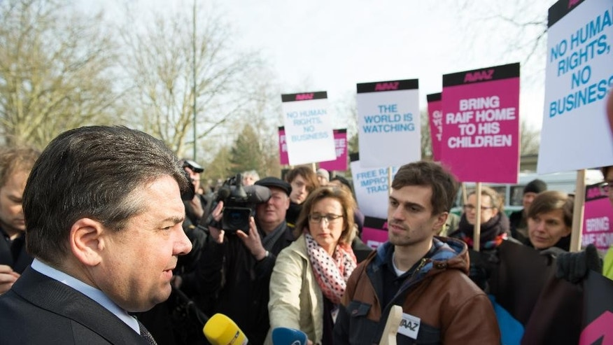 In this Saturday March 7, 2015 picture activists of the global civic movement Avaaz hand over signatures of an online petition to Germany's Minister of Economic Affairs and Energy,  Sigmar Gabriel, left, during a demonstration in front of the military airport of Tegel Berlin.  Gabriel, stopped on his way to board a plane to Saudi Arabia. The  petition wants to help free the Saudi Blogger  Raif Badawi, Shortly before meeting with the Saudi king on Sunday, German vice chancellor Sigmar Gabriel criticized a court-ordered punishment against the  Saudi blogger who was sentenced to 10 years in prison and 1,000 lashes for insulting Islam on a liberal blog.   (AP Photo/dpa, Bernd von Jutrczenka)
