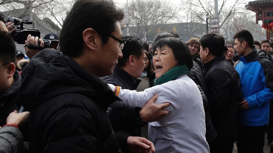Dai Shuqin, whose sister was on board Malaysia Airlines Flight 370 that went missing on March 8, 2014, is stopped by policemen as she speaks to journalists near Yonghegong Lama Temple during a gathering of family members of the missing passengers, in Beijing Sunday, March 8, 2015. Families of the 239 people on board Malaysia Airlines Flight 370 on Sunday marked the anniversary of the plane's disappearance, vowing to never give up on the desperate search for wreckage and answers to the world's biggest aviation mystery. (AP Photo/Andy Wong)
