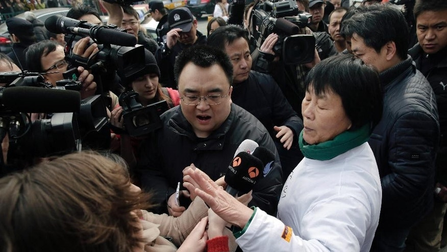 Dai Shuqin, front right, and Jiang Hui, rear right, relatives of passengers on board the Malaysia Airlines Flight 370 that went missing on March 8, 2014, is intervened by policemen as they try to speak to journalists near Yonghegong Lama Temple during a gathering of family members of the missing passengers, in Beijing Sunday, March 8, 2015. Families of the 239 people on board Malaysia Airlines Flight 370 on Sunday were marking the anniversary of the plane's disappearance with a vow to never give up on the desperate search for wreckage and answers to the world's biggest aviation mystery. (AP Photo/Andy Wong)