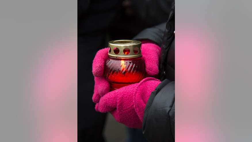 A mourner following the Russian tradition of memorialising a person nine days after a death holds a votive candle at the place where Boris Nemtsov, a charismatic Russian opposition leader and sharp critic of President Vladimir Putin, was gunned down on Friday, Feb. 27, 2015 near the Kremlin, in Moscow, on Saturday, March 7, 2015.  Two suspects have been detained in the killing a week ago of opposition politician Boris Nemtsov, the head of Russia's federal security service said Saturday, an announcement received with both skepticism and reserved satisfaction by some of Nemtsov's comrades.(AP Photo/Alexander Zemlianichenko)