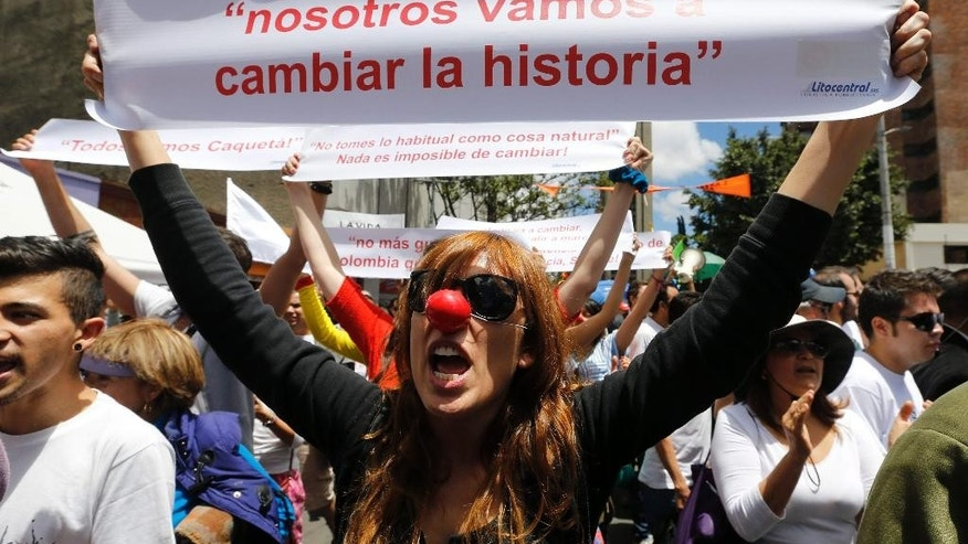 "A woman shouts: ""No more violence, we want peace, life is sacred!"" during a march coined ""March For Life"" in Bogota, Colombia, Sunday, March 8, 2015. Her sign reads in Spanish ""We're going to change history.""  Opposition leaders questioned the legitimacy of the march, saying the government awarded a contract to an NGO founded by Bogota's former Mayor Antanas Mockus to organized the march as a way to promote the ongoing peace talks between the government and FARC guerrilla group. (AP Photo/Fernando Vergara)"