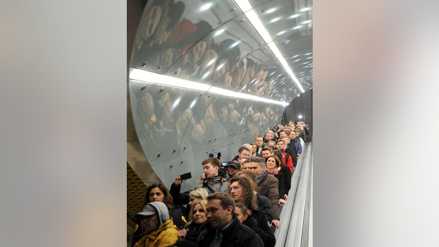 First passengers arrive at the Swietokrzyska station to take a ride on Warsaw's second subway line as it opens, in Warsaw, Poland, Sunday, March 8, 2015. The 6-kilometer (4-mile) line runs East-West and some 8 meters (26 feet) under the Vistula river, linking the eastern Praga district with the downtown. The opening was scheduled for the fall of 2013, but findings of buried, unexploded wartime bombs, and a major water leakage that flooded a nearly-finished station delayed the work. (AP Photo/Alik Keplicz)