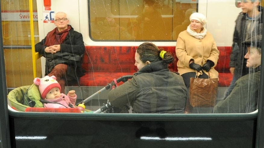 First passengers take a ride on Warsaw's second subway line as it opens, in Warsaw, Poland, Sunday, March 8, 2015. The 6-kilometer (4-mile) line runs East-West and some 8 meters (26 feet) under the Vistula river, linking the eastern Praga district with the downtown. The opening was scheduled for the fall of 2013, but findings of buried, unexploded wartime bombs, and a major water leakage that flooded a nearly-finished station delayed the work. (AP Photo/Alik Keplicz)