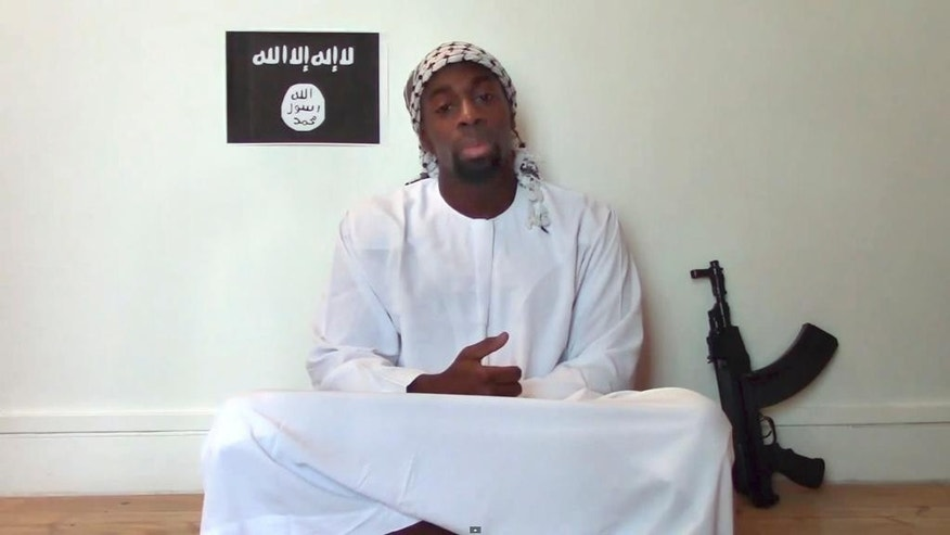 This file image made from a video posted online by militants in January shows slain hostage-taker Amedy Coulibaly, who shot  a policewoman and four hostages at a kosher grocery in Paris, with a gun in front of an ISIS emblem as he defends the Paris attacks carried out on the satirical newspaper, police and a Jewish store.