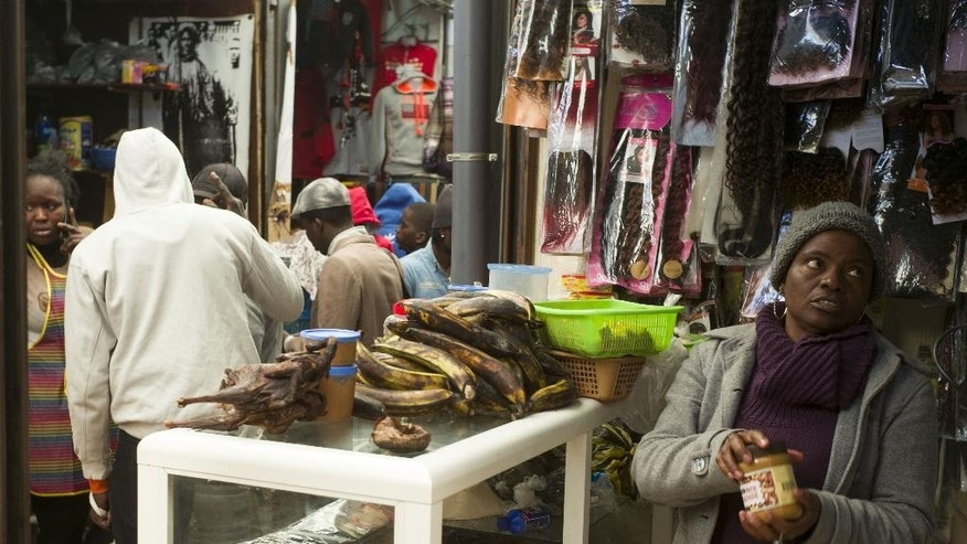 In this photo taken Tuesday, Feb. 24, 2015 Ivory Coast's Marthe N'Dri, right, works in her cosmetics and food products shop in the Senegalese souk in Casablanca, Morocco. Marthe N'Dri began her beauty business in Morocco just by going to people's homes to do braids and hair weaves, using skills she picked up as a beautician in her native Ivory Coast. Now she wants to add these skills to her tiny corner stall in the narrow warren of alleys known as the Senegalese Market in Casablanca. Next to the racks of hair extensions, cosmetics, plantains and bags of manioc, the plan is to put in a chair and do makeovers with the help of local organization providing business advice to immigrants. It is simple dreams like this that could be the future face of immigration in Morocco. (AP Photo/Abdeljalil Bounhar)