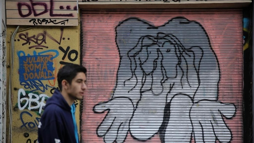A man walks past a shop with its shutter painted with a mural, in central Athens on Monday, March 9, 2015. Eurozone finance ministers will discuss about Greece at a Eurogroup meeting on Monday, as Athens had submitted seven reform proposals. (AP Photo/Petros Giannakouris)
