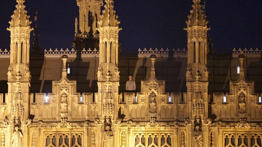 In this Saturday, March 7, 2015 photo, an unidentified man stands of the roof of the Palace of Westminster, the seat of Parliament in Britain, in London. British police have detained a man who spent the night on the roof of the Palace of Westminster on suspicion of criminal damage and trespassing. Scotland Yard said Sunday it was too early to know why the 23-year-old made his way to the top of Neo-Gothic masterpiece. The roof of the palace along the River Thames has long served as favored location for stunts by campaigners, such as those opposing the construction of another runway at Heathrow. Emergency services spotted the man just after 9 p.m. Saturday and he was detained early Sunday. (AP Photo/Yui Mok, PA Wire)      UNITED KINGDOM OUT      -      NO SALES      -     NO ARCHIVES