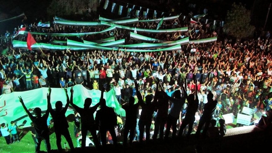 FILE - In this taken on Saturday, July 7, 2012 file citizen journalism image provided by Kafarsouseh Revolt, purports to show protesters chanting slogans and carrying Syrian revolutionary flags during a demonstration in Kafar Souseh, Damascus, Syria. Now four years later, the activists' goals are eclipsed in a conflict many believe has become a choice between rule by Assad and rule by Islamic radicals and they prefer the former. Hopes of democracy seen distant in a wrecked nation where more than 220,000 people have been killed, countless of others maimed and millions dispersed in the worst humanitarian crisis of the 21st century. The conflict has bred extremism that has touched countries across the globe and instilled chaos, bloodshed and violence that may redraw the map of the Middle East. (AP Photo/Kafarsouseh Revolt, File)