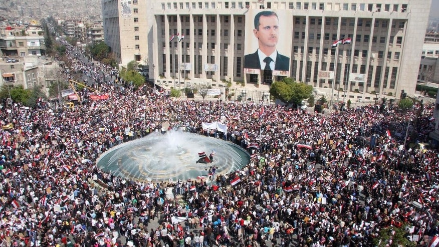 FILE - In this Tuesday, March 29, 2011 file photo, pro-Syrian President Bashar Assad protesters shoutslogans as they demonstrate to show their support for him, in Damascus, Syria. Now four years later, the activists' goals are eclipsed in a conflict many believe has become a choice between rule by Assad and rule by Islamic radicals and they prefer the former. Hopes of democracy seen distant in a wrecked nation where more than 220,000 people have been killed, countless of others maimed and millions dispersed in the worst humanitarian crisis of the 21st century. The conflict has bred extremism that has touched countries across the globe and instilled chaos, bloodshed and violence that may redraw the map of the Middle East. (AP Photo/Bassem Tellawi, File)