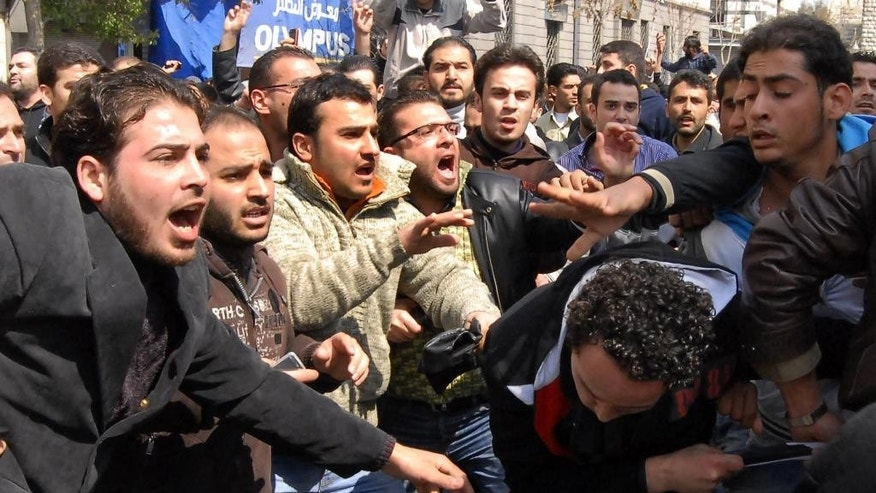 FILE - In this Friday, March 25, 2011 file photo, anti-Syrian government protesters, left, and pro-government, right, clash after Friday prayers in Damascus, Syria. Now four years later, the activists' goals are eclipsed in a conflict many believe has become a choice between rule by Bashar Assad and rule by Islamic radicals and they prefer the former. Hopes of democracy seen distant in a wrecked nation where more than 220,000 people have been killed, countless of others maimed and millions dispersed in the worst humanitarian crisis of the 21st century. The conflict has bred extremism that has touched countries across the globe and instilled chaos, bloodshed and violence that may redraw the map of the Middle East. (AP Photo/Muzaffar Salman, File)