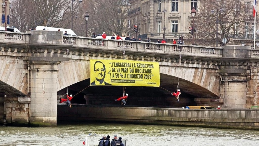 Greenpeace activists dangle a banner from a bridge over the Seine river next to the National Assembly in Paris, Monday March 9, 2015. Police broke up a stunt by Greenpeace activists who dangled from the bridge and unfurled banners on the river that call for cuts in nuclear power. The banner shows an image of President Francois Hollande and his campaign-trail pledge to reduce France's dependency on nuclear power from more than two-thirds of French energy production today. Hollande's Socialist government has promised to reduce that to 50 percent by 2025. (AP Photo/Remy de la Mauviniere)