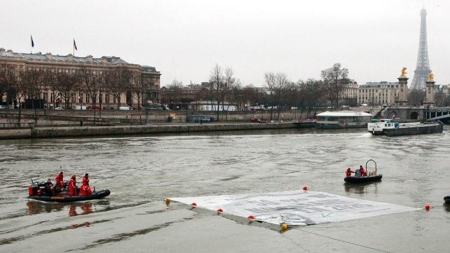 Greenpeace activists unfold a banner on the Seine River next to the National Assembly in Paris, Monday, March 9, 2015. Police broke up a stunt by Greenpeace activists who dangled from a bridge and unfurled banners on the river that call for cuts in nuclear power. The banner shows an image of President Francois Hollande and his campaign-trail pledge to reduce France's dependency on nuclear power from more than two-thirds of French energy production today. Hollande's Socialist government has promised to reduce that to 50 percent by 2025. (AP Photo/Remy de la Mauviniere)