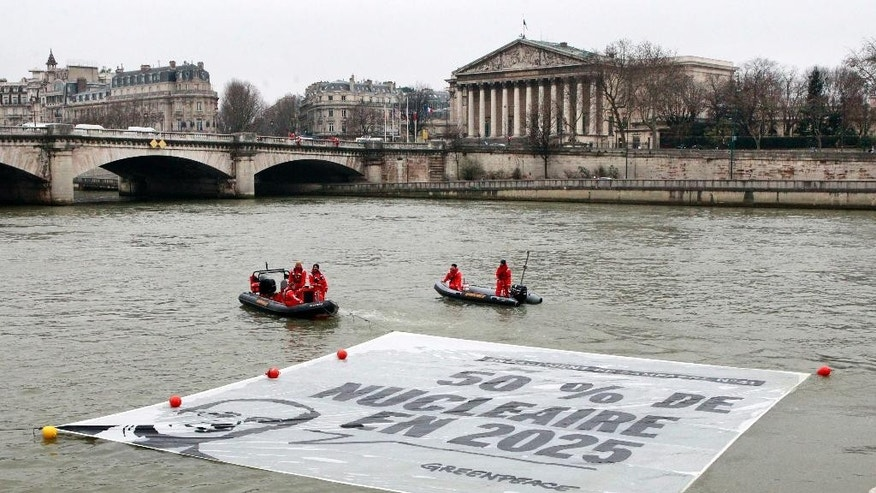 Greenpeace activists unfold a banner on the Seine River, next to the National Assembly, in the background, in Paris, Monday, March 9, 2015. Police broke up a stunt by Greenpeace activists who dangled from a bridge and unfurled banners on the river that call for cuts in nuclear power. The banner shows an image of President Francois Hollande and his campaign-trail pledge to reduce France's dependency on nuclear power from more than two-thirds of French energy production today. Hollande's Socialist government has promised to reduce that to 50 percent by 2025. (AP Photo/Remy de la Mauviniere)