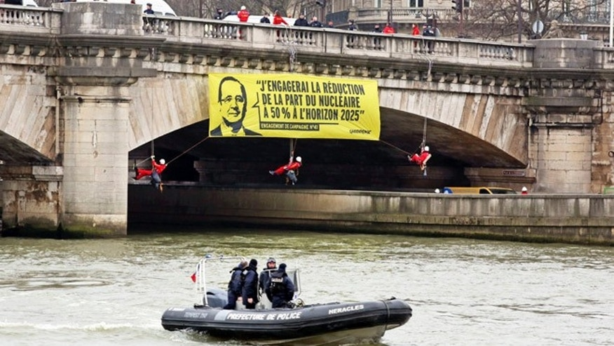 March 9, 2015: Greenpeace activists dangle a banner from a bridge over the Seine river next to the National Assembly in Paris. Police broke up a stunt by Greenpeace activists who dangled from the bridge and unfurled banners on the river that call for cuts in nuclear power. The banner shows an image of President Francois Hollande and his campaign-trail pledge to reduce Frances dependency on nuclear power from more than two-thirds of French energy production today. Hollandes Socialist government has promised to reduce that to 50 percent by 2025.