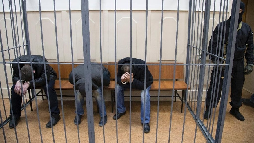 Three men, from the left: Tamerlan Eskerkhanov, Shagid Gubashev and Khamzad Bakhaev suspected of involvement in the killing of Boris Nemtsov sit in a court room in Moscow, Russia, Sunday, March 8, 2015. A Russian court on Sunday charged two men in the killing of leading opposition figure Boris Nemtsov and ordered three other suspects to remain in jail pending a decision on whether to file charges. (AP Photo/Ivan Sekretarev)