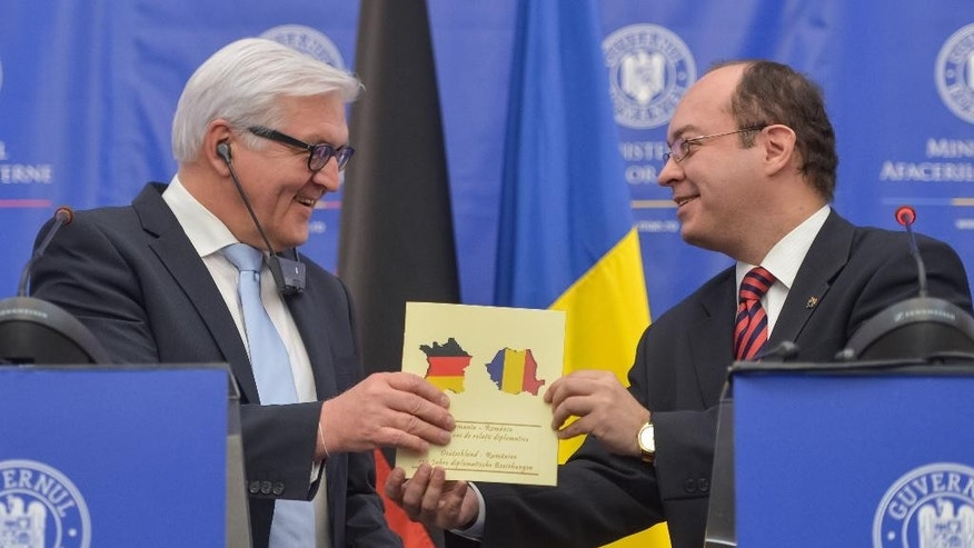 German Foreign Minister Frank-Walter Steinmeier, left, looks at his Romanian counterpart, Bogdan Aurescu, as he receives a document celebrating 135-years of Germany - Romania diplomatic relations, during a joint press conference, in Bucharest, Romania, Monday, March 9, 2015.  Steinmeier discussed the situation in Ukraine during talks with Romanian Foreign Minister Bogdan Aurescu, along with other matters of mutual interest. (AP Photo/Andreea Alexandru/Mediafax Foto) ROMANIA OUT