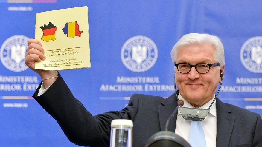 German Foreign Minister Frank-Walter Steinmeier holds up a document celebrating 135-years of German - Romania diplomatic relations, during a joint press conference, with his Romanian counterpart, Bogdan Aurescu, in Bucharest, Romania, Monday, March 9, 2015. The document mistakenly carries the shape of France covered in the German flag colors instead of Germany. (AP Photo/Andreea Alexandru, Mediafax) ROMANIA OUT