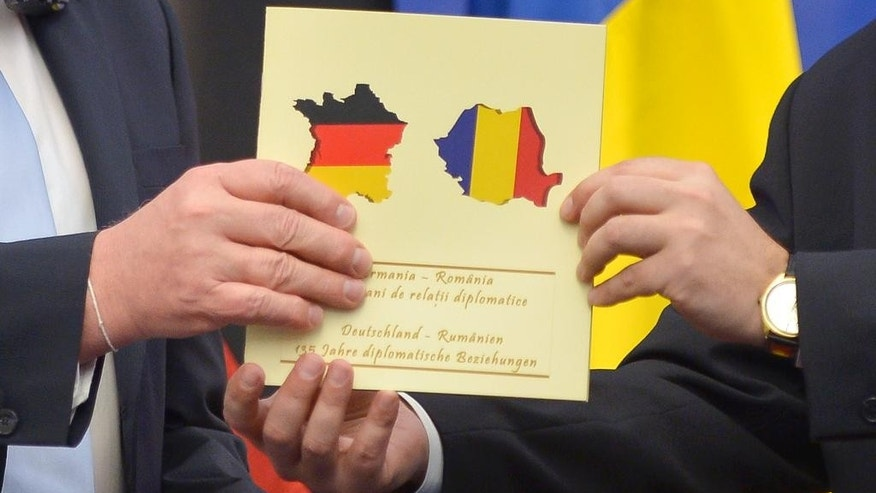 German Foreign Minister Frank-Walter Steinmeier, left, looks at his Romanian counterpart, Bogdan Aurescu, as he receives a document celebrating 135-years of German - Romanian diplomatic relations, during a joint press conference, in Bucharest, Romania, Monday, March 9, 2015. The document mistakenly carries the shape of France covered in the German flag colors instead of Germany. (AP Photo/Andreea Alexandru, Mediafax) ROMANIA OUT