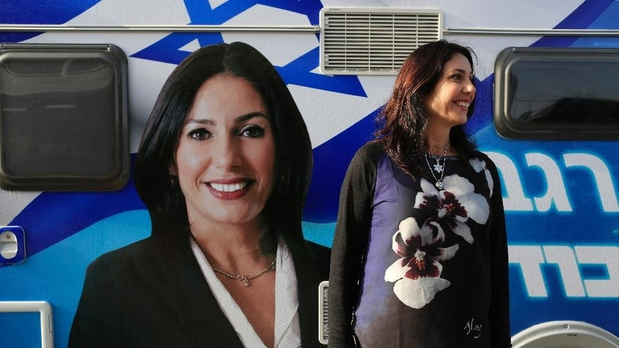 In this photo taken Feb. 9, 2015, Miri Regev stands in front of her campaign caravan in the southern Israeli town of Netivot. The boisterous legislator trounced established male politicians, including Defense Minister Moshe Yaalon, to reach the Likud party's fifth spot. (AP Photo/Tsafrir Abayov)