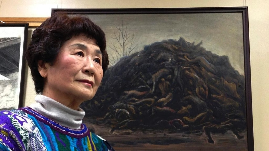 In this Feb. 11 2015 photo, Haruyo Nihei speaks next to a painting depicting a pile of victims of Tokyo Firebombing at the Center of the Tokyo Raids and War Damage. Nihei was only 8-years-old when the biggest attack of the war, the firebombing of central Tokyo, killed over 100,000 people and left hundreds of thousands more homeless. She fled with her family and watched as many others were burned alive. As the flames swept over her, she was sheltered by her father and many others who piled on top of them who suffocated or burned to death. (AP Photo/Mari Yamaguchi)