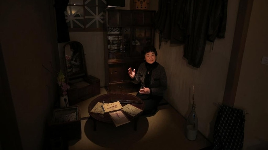 In this March 1, 2015 photo, Haruyo Nihei speaks at a room depicting the situation at that time of WWII under the blackout order at the Center of the Tokyo Raids and War Damage. Nihei was only 8-years-old when the biggest attack of the war, the firebombing of central Tokyo, killed over 100,000 people and left hundreds of thousands more homeless. She fled with her family and watched as many others were burned alive. As the flames swept over her, she was sheltered by her father and many others who piled on top of them who suffocated or burned to death.(AP Photo/Eugene Hoshiko)