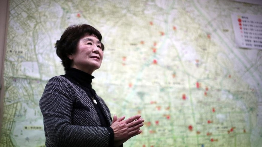 In this March 1, 2015 photo, Haruyo Nihei speaks in front of a map of damaged area of 1945's Tokyo Firebombing at the Center of the Tokyo Raids and War Damage. Nihei was only 8-years-old when the biggest attack of the war, the firebombing of central Tokyo, killed over 100,000 people and left hundreds of thousands more homeless. She fled with her family and watched as many others were burned alive. As the flames swept over her, she was sheltered by her father and many others who piled on top of them who suffocated or burned to death.(AP Photo/Eugene Hoshiko)