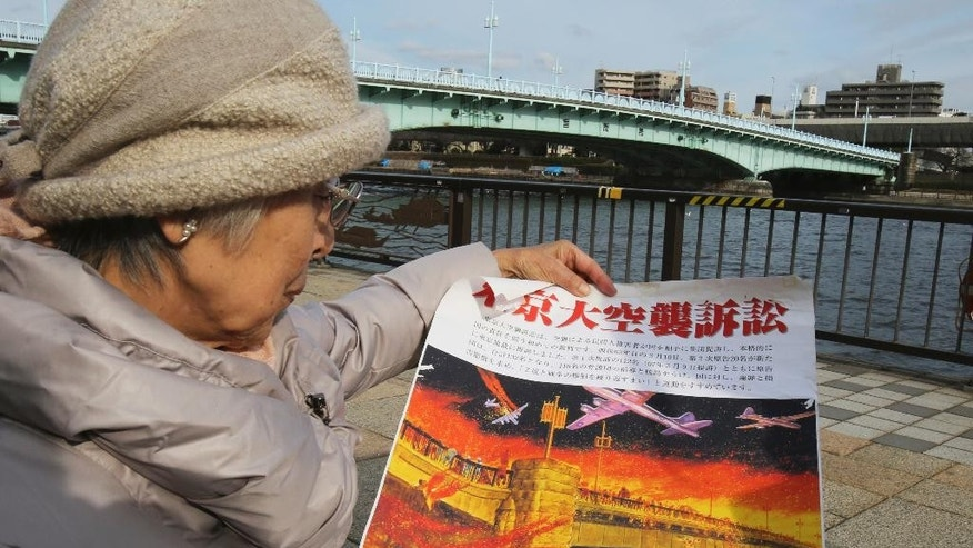 In this March 6, 2015 photo, Michiko Kiyo-oka, 91, holds a banner read as Tokyo Firebombing lawsuit at the riverside of Sumida river near the Asakusa district in Tokyo. Kiyo-oka, a city government worker and daughter of traditional entertainers, ran with her parents and sister toward the Sumida river, crowding with many others under the Kototoi Bridge. Kiyo-oka managed to avoid being pushed into the deep water, and her mother also survived at the water's edge. But her sister swam for a wooden post that caught fire and her father died trying to save her. Hundreds of people drowned, suffocated or were burned to death as the water's surface, slick with napalm, caught fire. (AP Photo/Koji Sasahara)