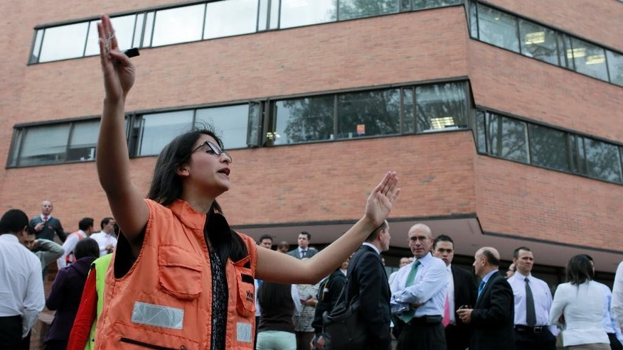 A woman directs people evacuating a building in Bogota after an earthquake shook eastern Colombia causing buildings to sway Tuesday, March 10, 2015. The quake had a magnitude of 6.2 and was centered near the city of Bucaramanga, about 175 miles (280 kilometers) north of Bogota, according to the U.S. Geological Survey. There were no immediate reports of damage or injuries. (AP Photo/Ricardo Mazalan)
