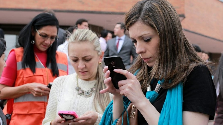 Women use their smart phones after the building where they work in Bogota was evacuated due to an earthquake that shook eastern Colombia causing buildings to sway in the capital Tuesday, March 10, 2015. The quake had a magnitude of 6.2 and was centered near the city of Bucaramanga, about 175 miles (280 kilometers) north of Bogota, according to the U.S. Geological Survey. There were no immediate reports of damage or injuries. (AP Photo/Ricardo Mazalan)