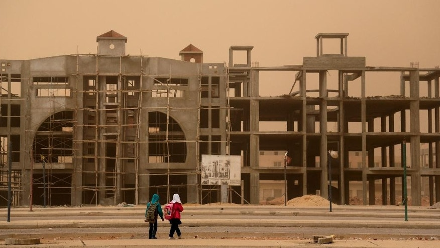 FILE - In this Feb. 11, 2015 file photo, young students walk to their homes during a sandstorm in 6 October city, a suburb southwest of Cairo, Egypt. A much-hyped investment conference opens in Egypt's Red Sea resort of Sharm el-Sheikh Friday, March 13, 2015. Egyptian President Abdel-Fattah el-Sissi the former army chief who overthrew an elected but divisive Islamist president a year and a half ago, has staked his legitimacy on boosting the sagging economy, and his government has set high hopes for the conference. (AP Photo/Mosa'ab Elshamy, File)