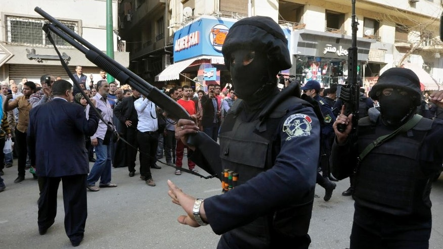 FILE - In this March 2, 2015 file photo, masked policemen patrol the site of a bombing near the Egyptian High Court, in Cairo, Egypt. A much-hyped investment conference opens in Egypt's Red Sea resort of Sharm el-Sheikh Friday, March 13, 2015, and its message is ubiquitous. The conference follows an uptick in attacks ostensibly aimed at foreign companies, and contradictory messages by a government eager to describe itself as besieged by regular terrorist attacks but simultaneously safe for foreigners. (AP Photo/Amr Nabil, File)