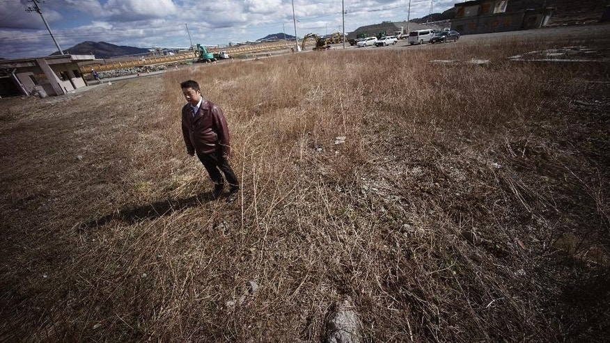 "In this Thursday, March 5, 2015 photo, Michihiro Kono, president of Yagisawa Syoten Co., stands at the site of his company's headquarters located before the 2011 tsunami in Rikuzentakata, Iwate Prefecture, northeastern Japan, Thursday, March 5, 2015. The traditional soy-sauce maker, destroyed by the giant tsunami four years ago, has made a comeback, defying tsunami-scale odds. The secret lies in a little white bottle, named ""the miracle,"" which holds the special ingredients that were passed down for decades. (AP Photo/Eugene Hoshiko)"