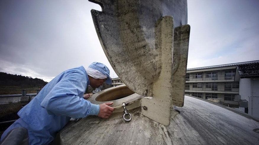 "In this Thursday, March 5, 2015 photo, a worker of Yagisawa Syoten Co., checks a soy source tank of the company's new factory in Ichinoseki, Iwate Prefecture, northeastern Japan. The traditional soy-sauce maker, destroyed by a giant tsunami four years ago, has made a comeback, defying tsunami-scale odds. The secret lies in a little white bottle, named ""the miracle,"" which holds the special ingredients that were passed down for decades. (AP Photo/Eugene Hoshiko)"