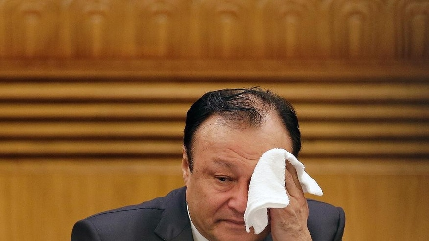 Shohrat Zakir, chairman of the Xinjiang Uyghur Autonomous Region, wipes his sweat during the Xinjiang delegation group's meeting on the sideline of the National People's Congress at the Great Hall of the People in Beijing Tuesday, March 10, 2015. Chinese officials said Tuesday that members of the country's Muslim Uighur ethnic minority have gone overseas to fight with the Islamic State group, which controls sections of Syria and Iraq, and returned to take part in plots at home. (AP Photo/Andy Wong)