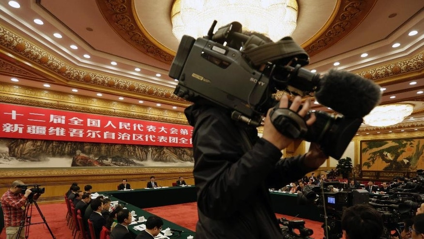 Journalists film a meeting of the Xinjiang delegation group on the sideline of the National People's Congress at the Great Hall of the People in Beijing Tuesday, March 10, 2015. Chinese officials said Tuesday that members of the country's Muslim Uighur ethnic minority have gone overseas to fight with the Islamic State group, which controls sections of Syria and Iraq, and returned to take part in plots at home. (AP Photo/Andy Wong)