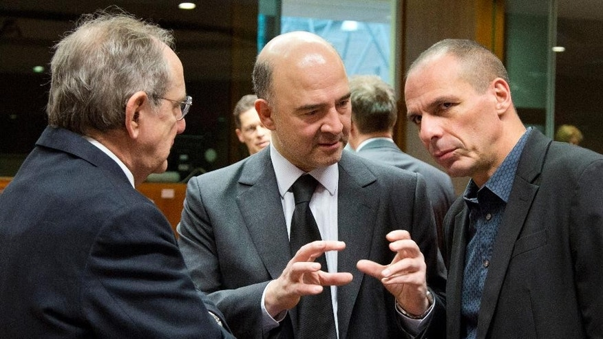 Greek Finance Minister Yanis Varoufakis, right, speaks with European Commissioner for the Economy Pierre Moscovici, center, and Italian Finance Minister Pier Carlo Padoan, left, during a meeting of EU finance ministers at the EU Council building in Brussels on Tuesday, March 10, 2015. Ministers on Tuesday will discuss the EU's banking union, the European semester and strategic investment. (AP Photo/Virginia Mayo)